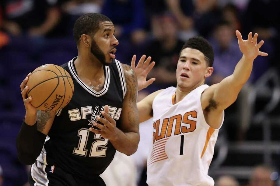 LaMarcus Aldridge of the Spurs looks to pass around Devin Booker of the Suns during the first half at Talking Stick Resort Arena on Dec. 15, 2016 in Phoenix. Photo: Christian Petersen /Getty Images / 2016 Getty Images