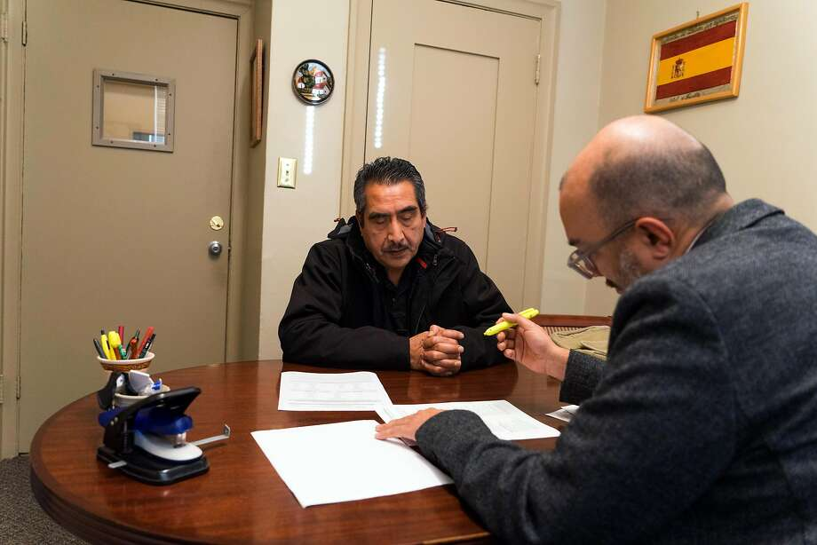 Beltrand Arellano (right) helps Efrain Salazar with his legal questions at Catholic Charities. Photo: James Tensuan, Special To The Chronicle