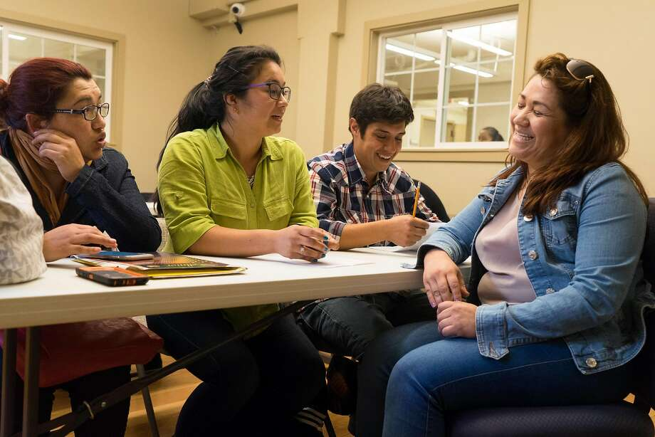 Domitza Quiroga (left), Katherine Medina, Alejandro Rodriguez and Milka Quiroga wait to get legal advice at Catholic Charities' weekly drop-in clinic in San Francisco for immigrants. Photo: James Tensuan, Special To The Chronicle