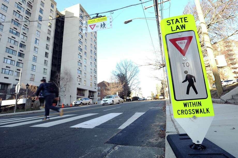 A student uses the crosswalk, which features a new flashing, hanging sign, outside Stamford High School in Stamford. Photo: Michael Cummo / Hearst Connecticut Media / Stamford Advocate