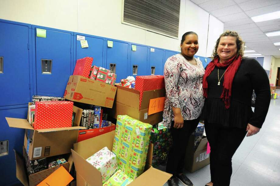 Melissa Bramble, right, and Margaret Giron pose next to presents gathered by the Angel Family program inside DOMUS in Stamford, Conn. on Thursday, Dec. 15, 2016. Bramble runs the progarm and Giron is a second-year recipient. Photo: Michael Cummo / Hearst Connecticut Media / Stamford Advocate