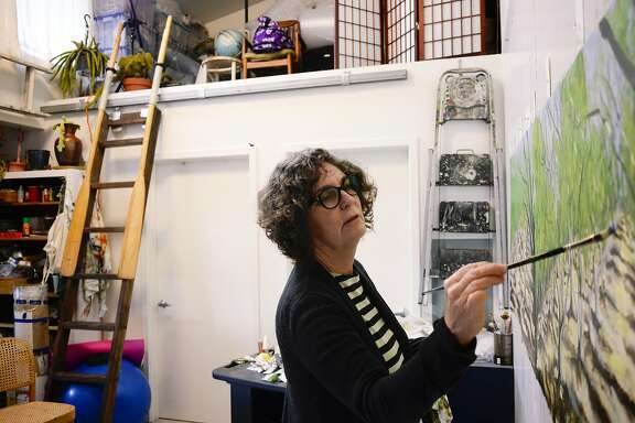 Margaret Niven, painter and teacher, works on a painting in her living space at the Tannery Art Center in Santa Cruz, CA, on Friday December 16, 2016. The Tannery gives artists an affordable space to work and live.