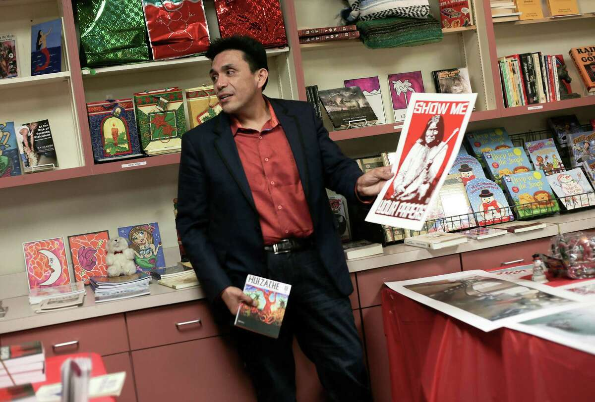 Tony Diaz shows some of the art and books that are for sale at the new store.