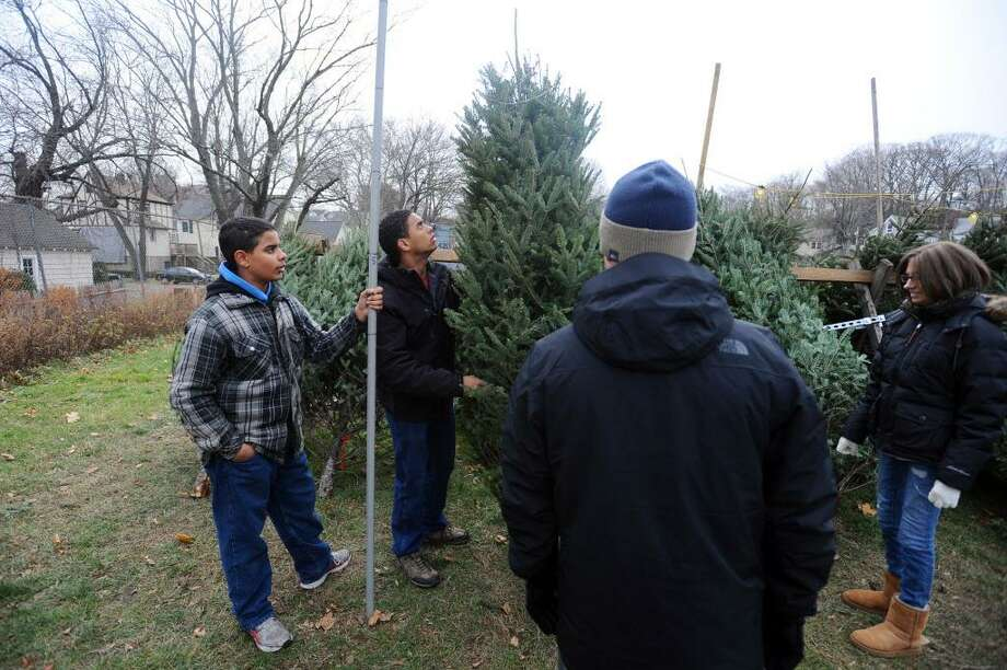 Thirteen-year-old Andrew Bagan, left, and 16-year-old Joseph Bagan, center, measure the height of a Christmas tree for customers during a tree and wreath sale in the parking lot behind Stamford High School in Stamford, Conn. on Sunday, Dec. 11, 2016. The Christmas Tree and Wreath sale benefits the Stamford High School band. Photo: Michael Cummo / Hearst Connecticut Media / Stamford Advocate