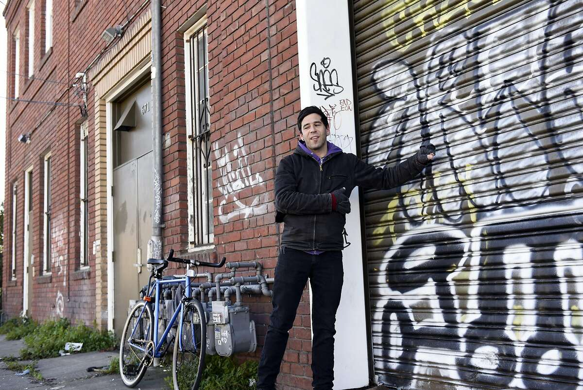 Jonah Strauss bangs on a roll up door of his former residence, the West Oakland arts hub, live-work space and home of anarchist bookseller AK Press that caught fire in March 2015, killing 2 people and forcing all of it's residents out, in Oakland, CA, on Friday, December 16, 2016.