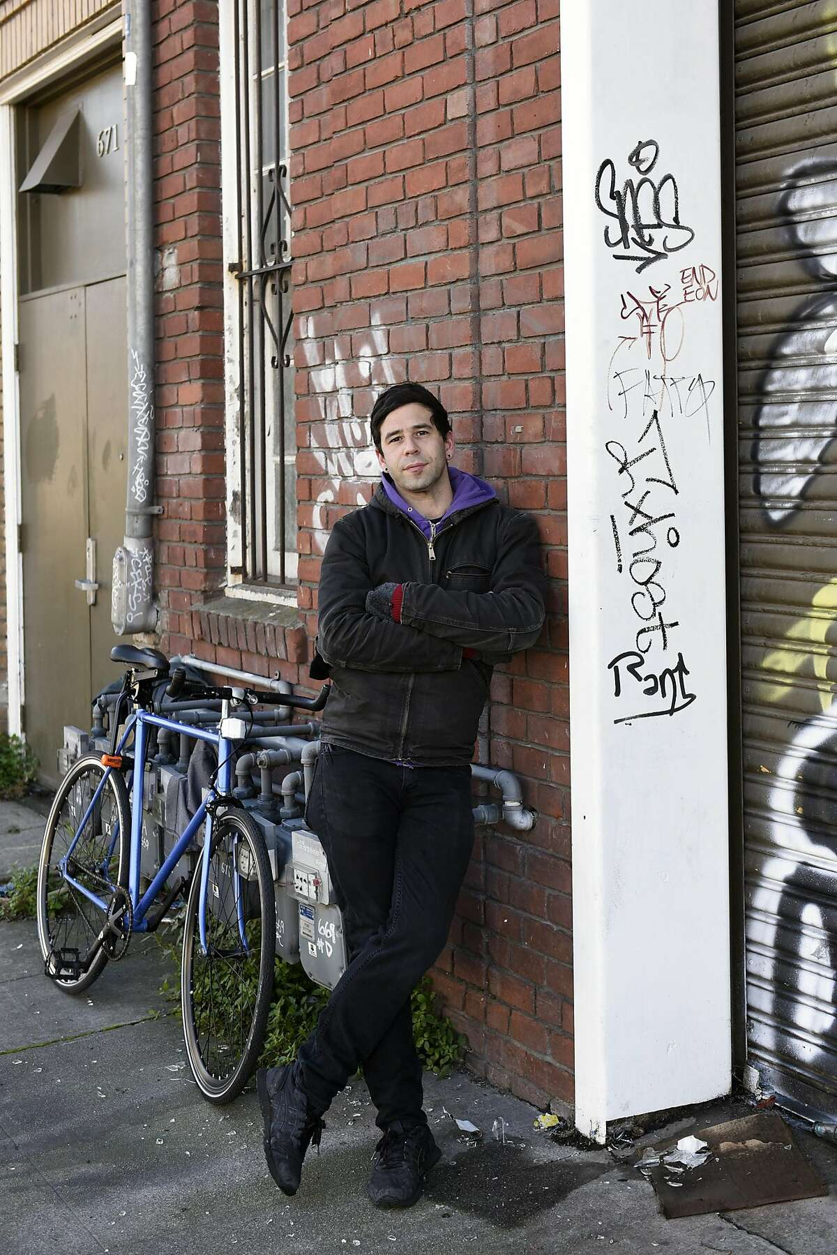 Jonah Strauss poses for a portrait in front of the West Oakland arts hub, live-work space and home of anarchist bookseller AK Press that caught fire in March 2015, killing 2 people and forcing all of it's residents out, in Oakland, CA, on Friday, December 16, 2016.