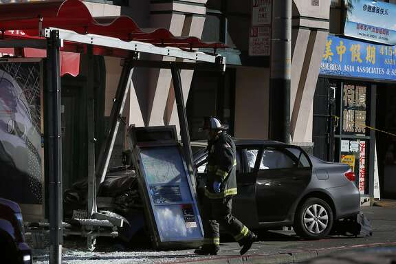 An emergency responder assesses a multiple-injury accident scene where a vehicle collided with a bus stop on Stockton Street between Sacramento and Clay Streets Dec. 16, 2016 in San Francisco, Calif.