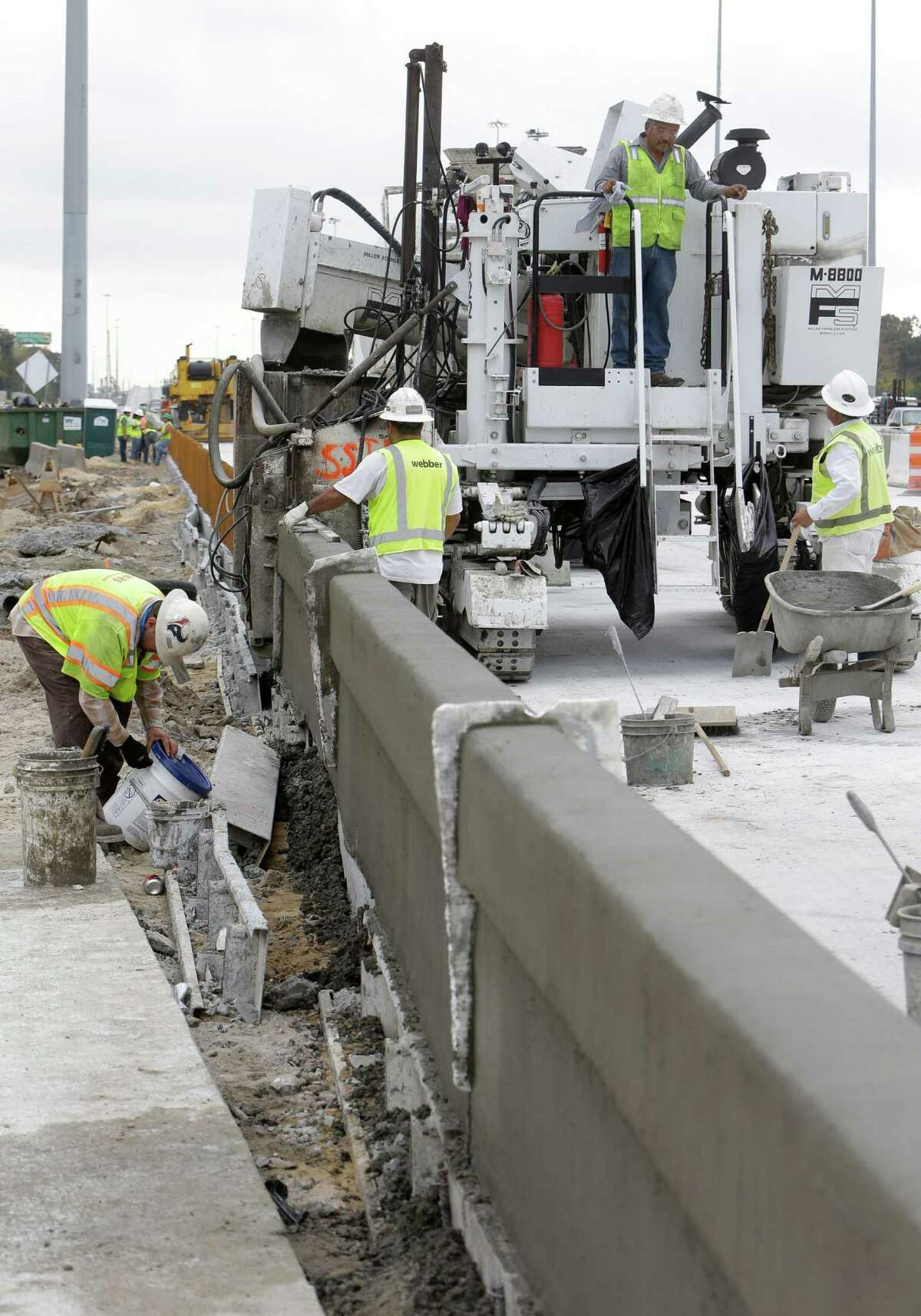 Workers place concrete rail along the new westbound main lanes of U.S. 290 near Hollister on Dec. 13.