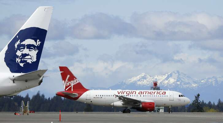 A Virgin America plane taxis past an Alaska Airlines plane waiting at a gate, Monday, April 4, 2016, at Seattle-Tacoma International Airport in Seattle. Alaska Airlines' parent company announced Monday that it will pay $2.6 billion to buy the Richard Branson-inspired, California-based Virgin America. (AP Photo/Ted S. Warren)