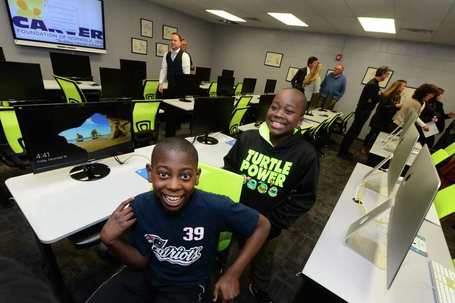 Alfred Remarais, 12, and Justin Thomas, 11, enjoy the George Washington Carver Community Center's new technology center, The Charlotte Naomi Horblit Technology Center, a state-of-the-art STEM education lab on the second floor of the Carver Center, following the ribbon cutting ceremony Friday, December 16, 2016, in Norwalk, Conn. The tech center has 32 workstations and includes iMac computers with Retina 5K displays, a 3D printer, a 3D scanner and video conferencing software to support blended learning.  Mayor Harry Rilling will be in attendance, along with Mark Feinberg and the Carver Board of Directors. Photo: Erik Trautmann / Hearst Connecticut Media / Norwalk Hour