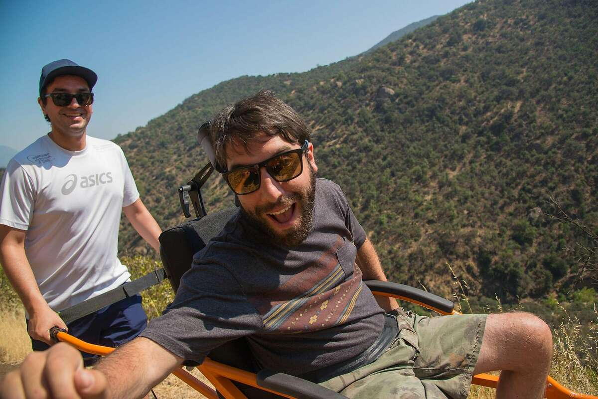 Francisco Aviles, left, carries Alvaro Silberstein while trekking Sunday, Dec. 11, 2016 in Santiago, Chile. Alvaro Silberstein wants to expand the places disabled people can go in the world. This week, the 31-year-old graduate student hopes to become the first person in a wheelchair to trek in three wild regions of primeval Torres del Paine National Park in Chilean Patagonia