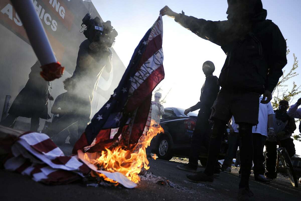 Protesters burn an American flag during a small march through downtown Oakland. President Obama gave a speech at the Fox Theater during a fundraising stop in downtown Oakland, CA Monday July 23rd, 2012