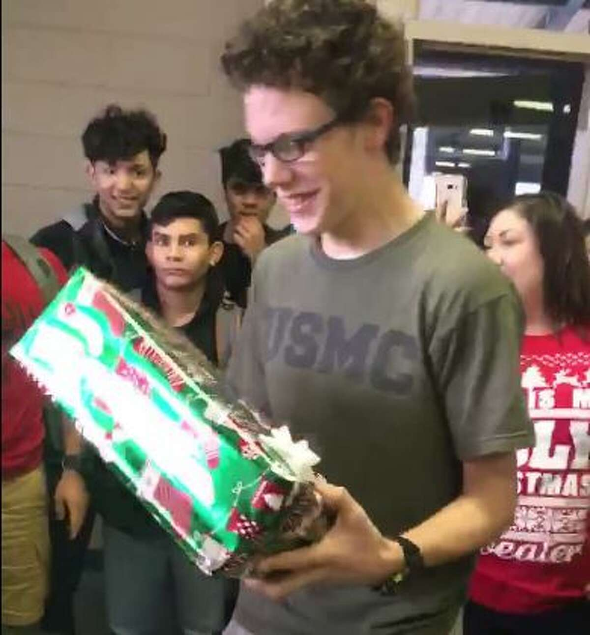 The look on Somerset High School Sophomore JR Gilbert's face is priceless as he opens a gift from his fellow high school students Friday Dec. 16, 2016.