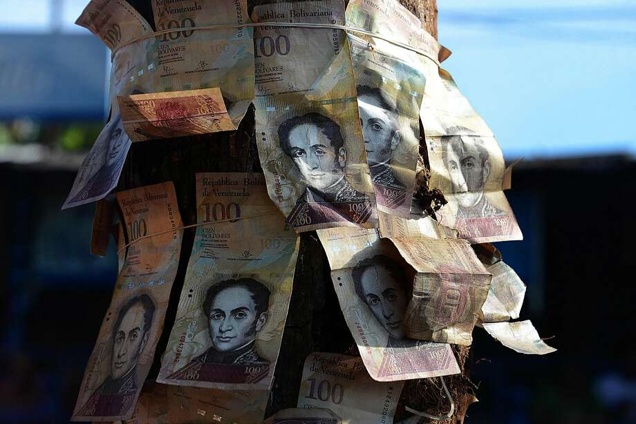 "People tie 100-Bolivar notes to a tree during a protest over lack of cash as the new bank notes have not yet appeared, at the ""Troncal 5"" road in San Cristobal in Venezuela's Tachira state, on December 16, 2016.    Venezuelans lined up to deposit 100-unit banknotes before they turned worthless, but replacement bills had yet to arrive, increasing the cash chaos in the country with the world's highest inflation. Venezuelans are stuck in currency limbo after President Nicolas Maduro ordered the 100-bolivar note -- the largest denomination, currently worth about three US cents -- removed from circulation in 72 hours. / AFP PHOTO / GEORGE CASTELLANOSGEORGE CASTELLANOS/AFP/Getty Images Photo: GEORGE CASTELLANOS, AFP/Getty Images"