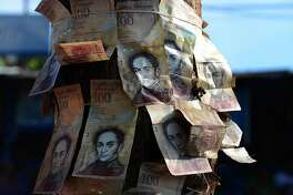 "People tie 100-Bolivar notes to a tree during a protest over lack of cash as the new bank notes have not yet appeared, at the ""Troncal 5"" road in San Cristobal in Venezuela's Tachira state, on December 16, 2016.    Venezuelans lined up to deposit 100-unit banknotes before they turned worthless, but replacement bills had yet to arrive, increasing the cash chaos in the country with the world's highest inflation. Venezuelans are stuck in currency limbo after President Nicolas Maduro ordered the 100-bolivar note -- the largest denomination, currently worth about three US cents -- removed from circulation in 72 hours. / AFP PHOTO / GEORGE CASTELLANOSGEORGE CASTELLANOS/AFP/Getty Images"