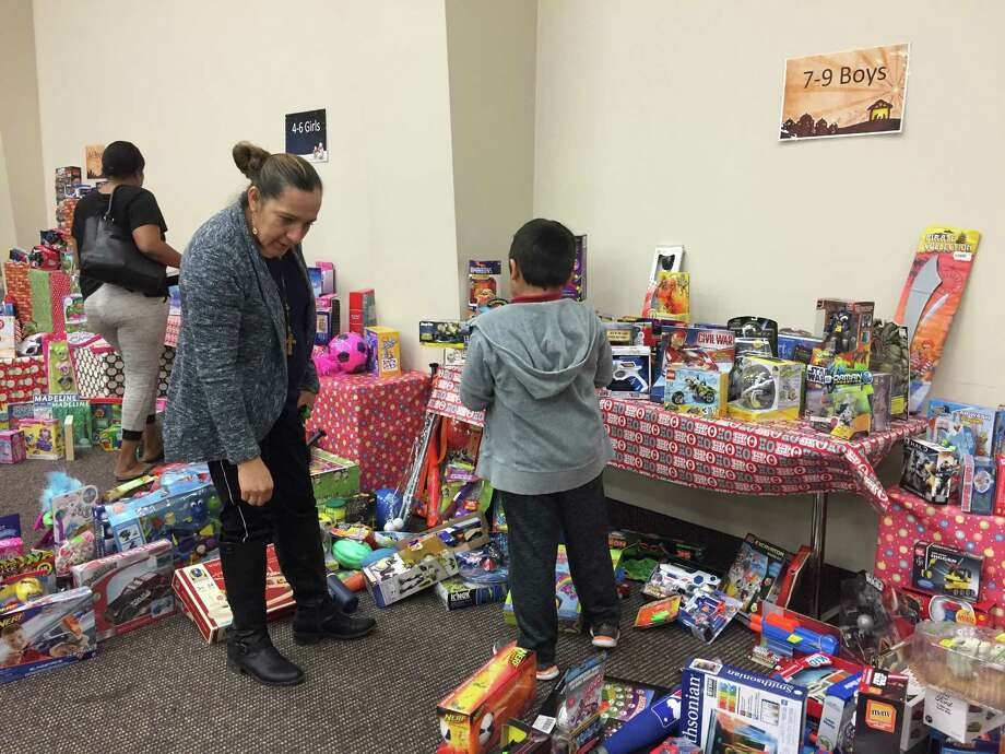 Severiana Gonzalez helps her son Chris, 7, pick out a toy Friday at World Christian Fellowship. Every year the Humble Area Assistance Ministries hosts a toy drive at Christmas to help families during the holidays. Photo: Julie Silva