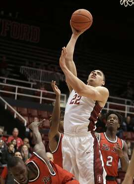 Stanford's Reid Travis (22) shoots over Cal State East Bay forward Lamine Mbodj, left, and Druce Asah (2) during the first half of an NCAA college basketball game Friday, Dec. 16, 2016, in Stanford, Calif. (AP Photo/Ben Margot)