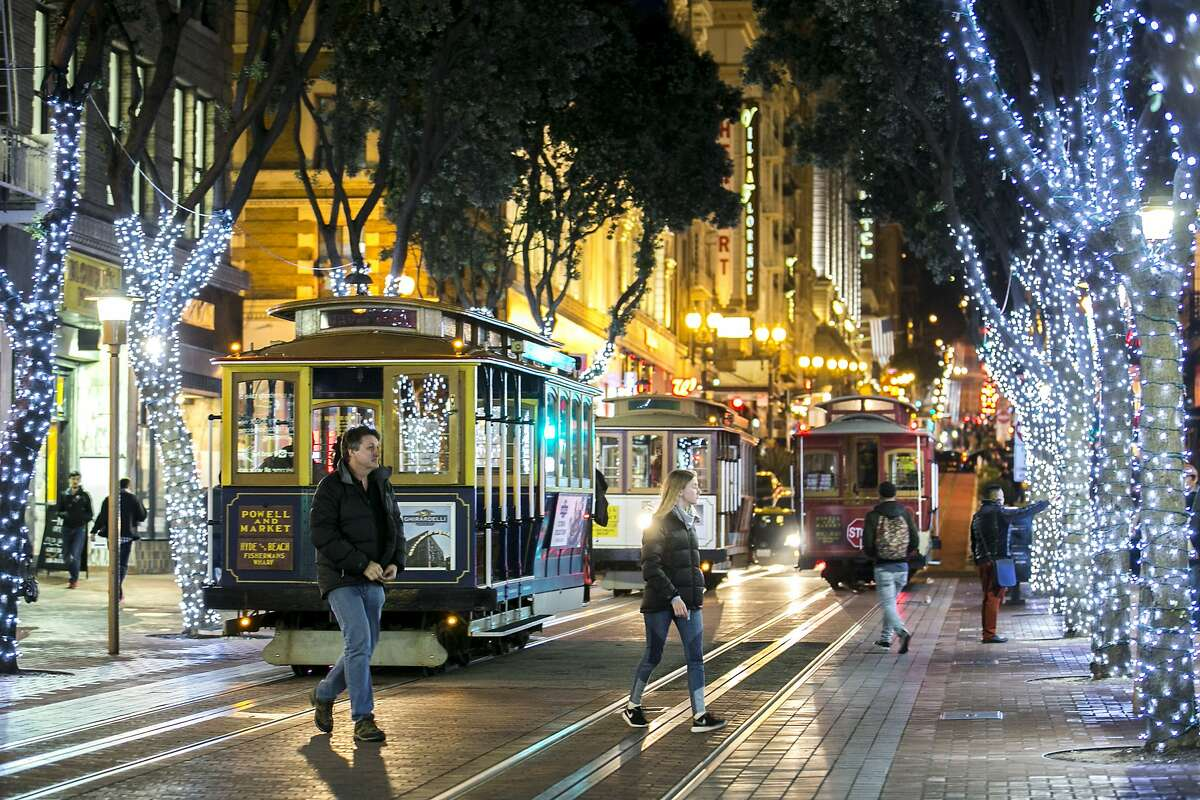 People walk downtown past cable cars on Friday, Dec. 16, 2016 in San Francisco, Calif.