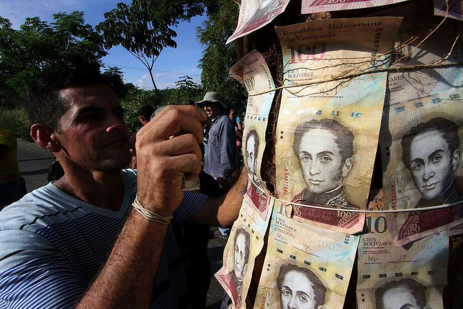 """People show 100-Bolivar notes during a protest over lack of cash as the new bank notes have not yet appeared, at the """"Troncal 5"""" road in San Cristobal in Venezuela's Tachira state, on December 16, 2016.    Venezuelans lined up to deposit 100-unit banknotes before they turned worthless, but replacement bills had yet to arrive, increasing the cash chaos in the country with the world's highest inflation. Venezuelans are stuck in currency limbo after President Nicolas Maduro ordered the 100-bolivar note -- the largest denomination, currently worth about three US cents -- removed from circulation in 72 hours. / AFP PHOTO / GEORGE CASTELLANOSGEORGE CASTELLANOS/AFP/Getty Images Photo: GEORGE CASTELLANOS, AFP/Getty Images"""