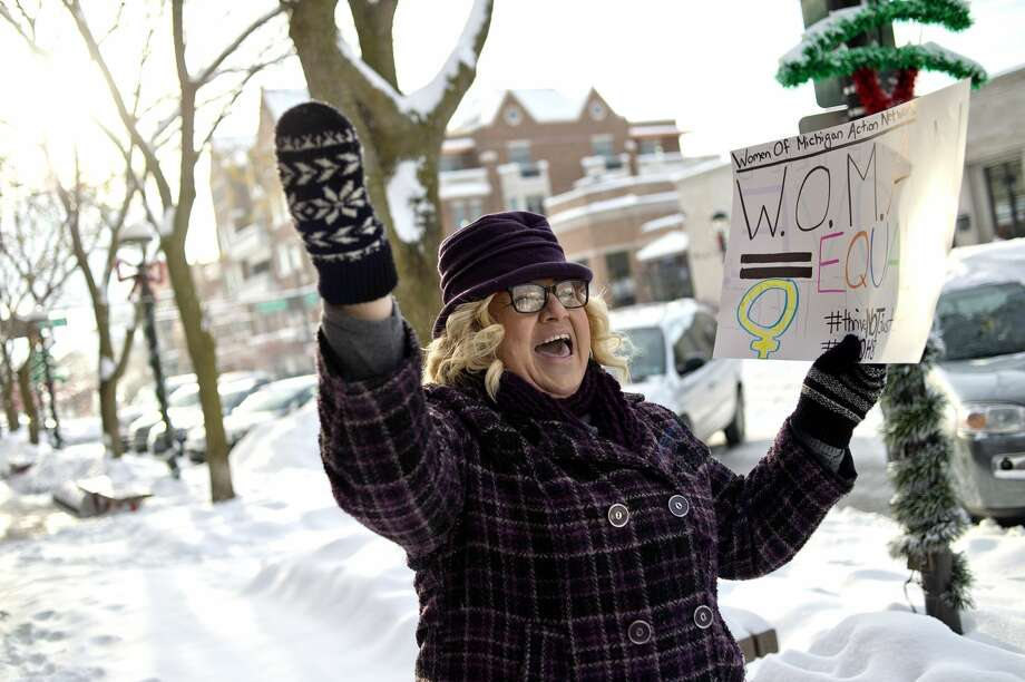 """Organizer Jody Liebmann leads the group in a chant on Saturday in downtown Midland. More than 30 people met at the corner of Gordon and Main streets for a rally and march to celebrate the resistance of policy and intolerance based on fear and hate. The event was hosted by the Women of Michigan Action Network (W.O.M.A.N.), a local group for positive change and resistance formed in response to the election of Donald Trump. The group marched between Gordon and Ashman streets and chanted slogans including, """"Show me what democracy looks like, this is what democracy looks like,"""" and """"Love not hate makes America great,"""" to name a few. The group also sang, """"America the Beautiful"""" and """"This Land Is Your Land."""" Photo: NICK KING 