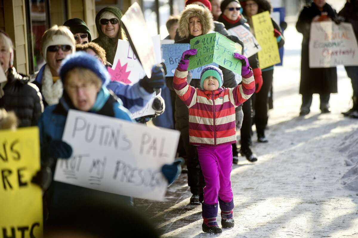 """Evangeline Rankin, 7, right, marches with a group on Saturday in downtown Midland. More than 30 people met at the corner of Gordon and Main streets for a rally and march to celebrate the resistance of policy and intolerance based on fear and hate. The event was hosted by the Women of Michigan Action Network (W.O.M.A.N.), a local group for positive change and resistance formed in response to the election of Donald Trump. The group marched between Gordon and Ashman streets and chanted slogans including, """"Show me what democracy looks like, this is what democracy looks like,"""" and """"Love not hate makes America great,"""" to name a few. The group also sang, """"America the Beautiful"""" and """"This Land Is Your Land."""""""