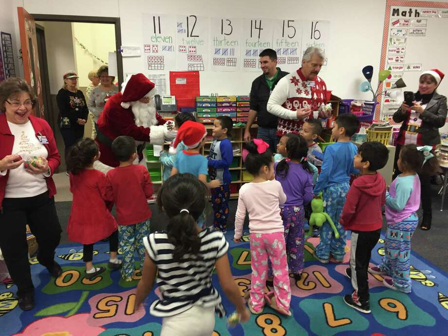 "Santa and members of the Conroe Noon Lions Club hosted ""Jingle Bell Bash"" at the adopted school of Reaves Elementary by handing out Christmas bells and loads of fun. Photo: Submitted"
