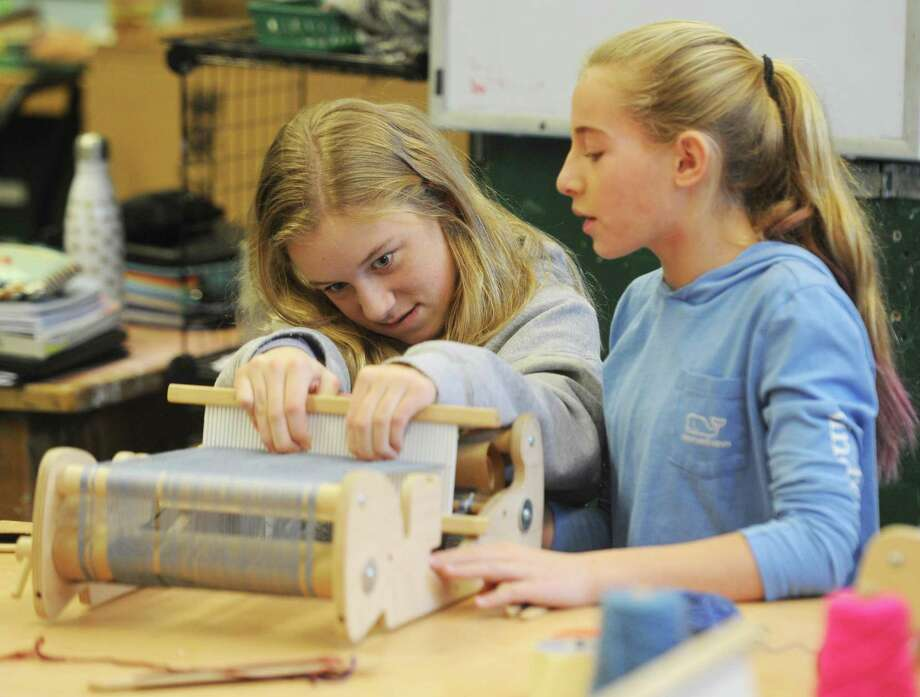 Seventh-graders Bennett Barth, left, and Avery Banks work on a loom art project at Eastern Middle School in Greenwich. Local guest artists Ruben Marroquin and Liz Squillace lent their artistic talents for a day to teach middle school students how to weave with a loom and give perspective about what life as an artist is like. Photo: Tyler Sizemore / Hearst Connecticut Media / Greenwich Time