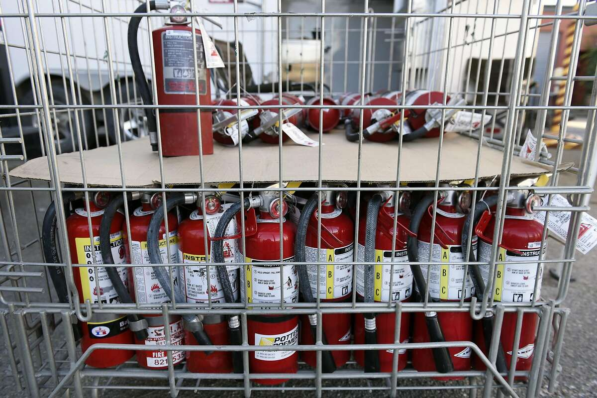 About 100 fire extinguishers donated by Bay Cities Pyrotector are set to be given away to members of the creative community who may live or work in a warehouse or DIY spaces, by organizers at the Kraftworks space in Oakland, CA, on Saturday, December 17, 2016.