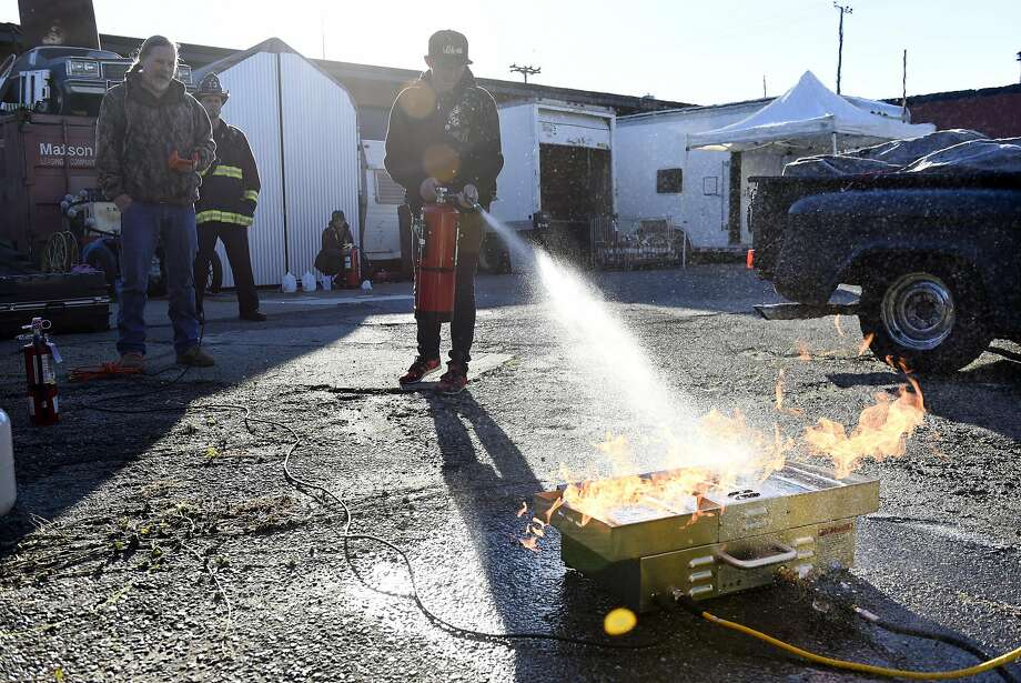 Volunteer Shane Sischo learns how to properly use a fire extinguisher during an event organized by members of the Kraftworks space in Oakland. Photo: Michael Short, Special To The Chronicle
