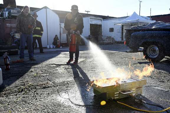 Event volunteer Shane Sischo tries out a simulation that teaches how to properly use a fire extinguisher during an event organized by members of the Kraftworks space to give away fire extinguishers and smoke detectors to members of the creative community who live or work in  warehouses or DIY spaces, in Oakland, CA, on Saturday, December 17, 2016.