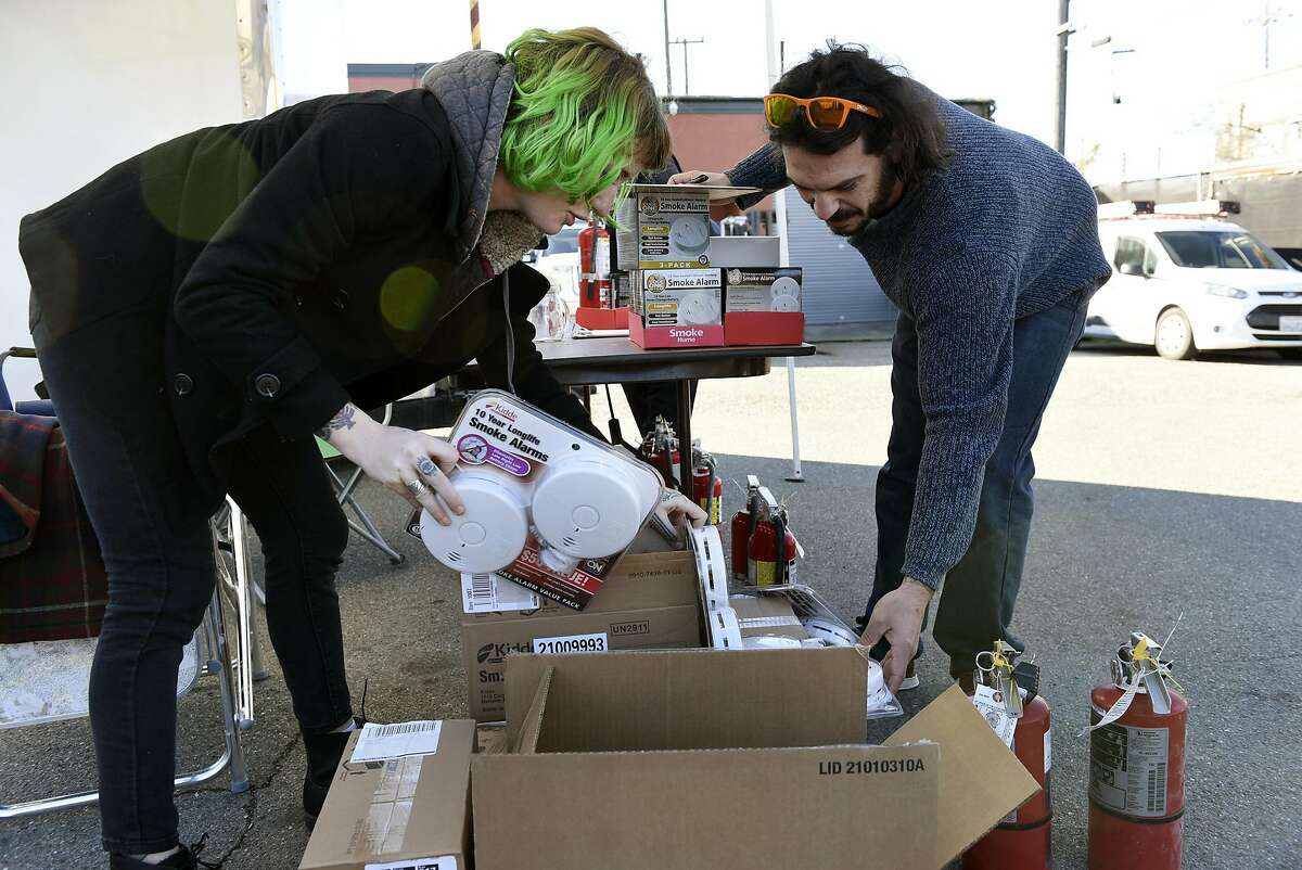 Oakland resident and event organizer H.L. Nelly, left, helps Rory Terrell, who manages the six Firehouse Art Collective locations in Berkeley and Emeryville, as he picks up smoke detectors and fire extinguishers for his spaces during an event organized by members of the Kraftworks space to give away fire extinguishers and smoke detectors to members of the creative community who live or work in warehouses or DIY spaces, in Oakland, CA, on Saturday, December 17, 2016.