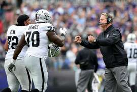 Oakland Raiders head coach Jack Del Rio, right, fist-bumps tackle Donald Penn (72) and offensive guard Kelechi Osemele after a Raiders touchdown in the first half of an NFL football game against the Baltimore Ravens, Sunday, Oct. 2, 2016, in Baltimore. (AP Photo/Gail Burton)