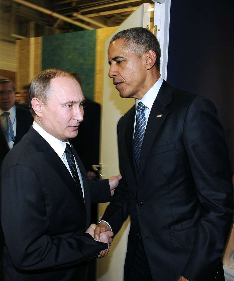 This file photo taken on November 30, 2015 shows Russian President Vladimir Putin (left) meeting with US President Barack Obama on the sidelines of the UN conference on climate change - COP21 in Le Bourget, on the outskirts of the French capital Paris.  Barack Obama on December 15, 2016 said the United States would retaliate against Russian hacking after the White House accused Vladimir Putin of direct involvement in cyberattacks designed to influence the US election.  Photo: MIKHAIL KLIMENTYEV, AFP/Getty Images