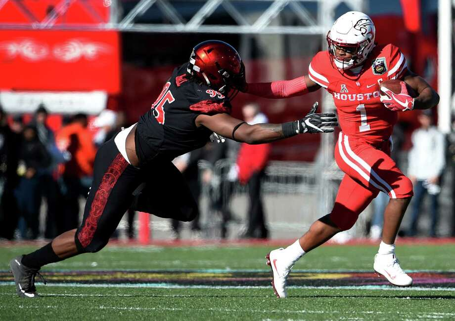 Houston quarterback Greg Ward Jr. (1) avoids a tackle from San Diego State defensive lineman Noble Hall during the first half of the Las Vegas Bowl NCAA college football game on Saturday, Dec. 17, 2016, in Las Vegas. (AP Photo/David Becker) Photo: David Becker, Associated Press / FR170737 AP