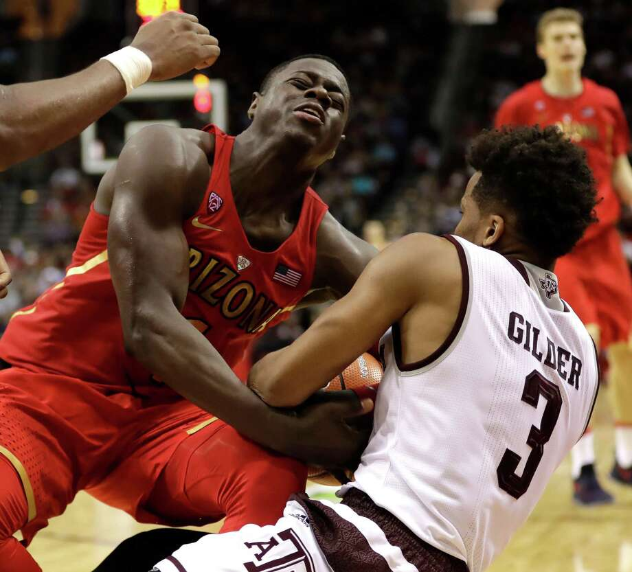 Texas A&M's Admon Gilder (3) forces a jump ball with Arizona's Rawle Alkins during the second half of an NCAA college basketball game Saturday, Dec. 17, 2016, in Houston. Arizona won 67-63. (AP Photo/David J. Phillip) Photo: David J. Phillip, Associated Press / Copyright 2016 The Associated Press. All rights reserved.