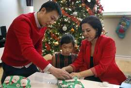 Tina Vossugh (right) wraps Christmas gifts with her husband Bo Chai and their daughter Lili Chai to prepare for the holidays at their home in Milpitas, Calif. on Saturday, Dec. 17, 2016. Neither Vossugh or Chai were raised as Christians but have decided to celebrate Christmas traditions with their 7-year-old daughter.