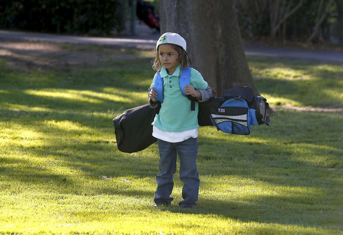 Yeshua Cuffy, 5, carries a golf bag as tall as he is at the municipal golf course in Palo Alto, Calif. on Saturday, Dec. 17, 2016. Bob Hoover founded the East Palo Alto Junior Golf program 25 years ago.