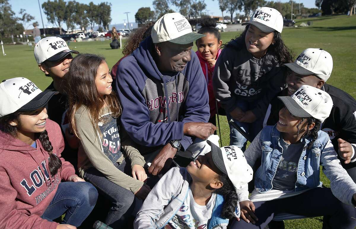 Budding golfers gather around Bob Hoover at the municipal golf course in Palo Alto, Calif. on Saturday, Dec. 17, 2016. Hoover founded the East Palo Alto Junior Golf program 25 years ago.