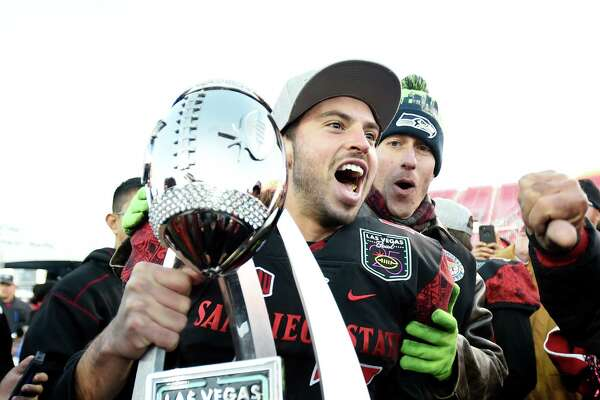 San Diego State wide receiver Marc Ellis reacts with the championship trophy after San Diego State defeated Houston in the Las Vegas Bowl NCAA college football game on Saturday, Dec. 17, 2016, in Las Vegas. San Diego State won 34-10. (AP Photo/David Becker)
