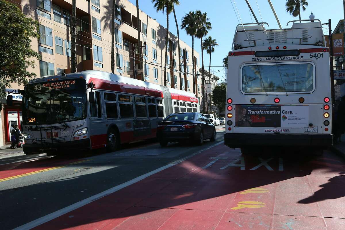 FILE--A car is seen driving between the red transit-only lanes at 16th and Mission St on Friday, Dec. 16 2016 in San Francisco. Muni recently approved new red lanes on Geary Boulevard between Stanyan and Gough streets.