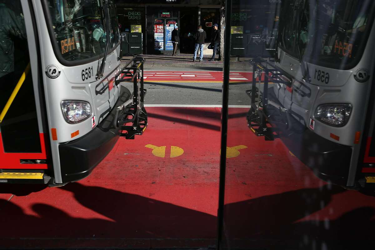 FILE--A bus using one of the red transit-only lanes is seen reflected in a sign at 16th and Mission St on Friday, Dec. 16 2016 in San Francisco. Muni recently approved new red lanes on Geary Boulevard between Stanyan and Gough streets.