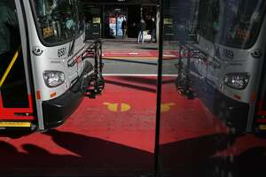 A bus using one of the red transit-only lanes is seen reflected in a sign at 16th and Mission St on Friday, December 16 2016 in San Francisco, Calif.