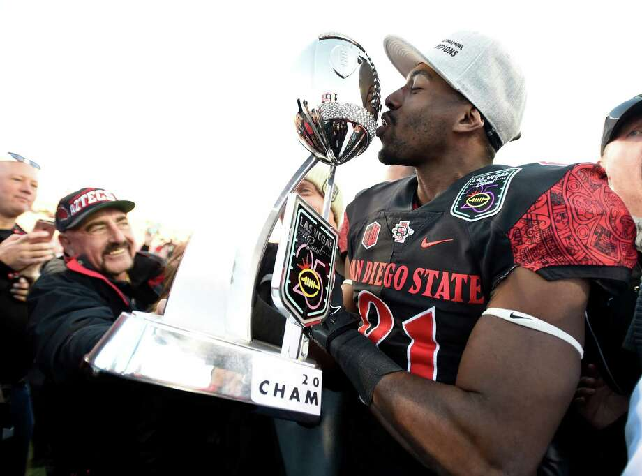 San Diego State wide receiver Eric Judge kisses the championship trophy after San Diego State defeated Houston 34-10 in the Las Vegas Bowl NCAA college football game Saturday, Dec. 17, 2016, in Las Vegas. (AP Photo/David Becker) Photo: David Becker, Associated Press / FR170737 AP