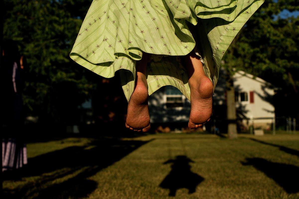 ERIN KIRKLAND   ekirkland@mdn.net Chloe, 7, swings in the backyard in Coleman on July 26.