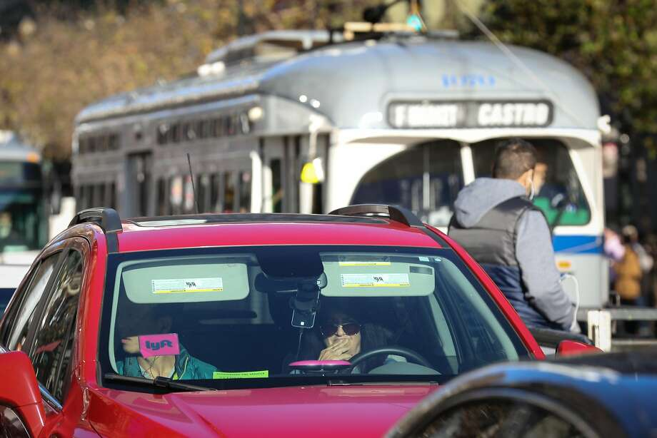 An Lyft car is seen on Market Street with the F train behind it in December. San Francisco is seeking court orders to force Uber and Lyft to provide data about drivers and rides in the city. Photo: Amy Osborne, Special To The Chronicle
