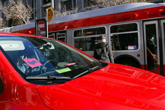 An Lyft car is seen next to a Muni stop on Market Street on Friday, December 17, 2016 in San Francisco, Calif.