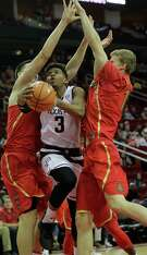Texas A&M guard Admon Gilder slices his way through two Arizona defenders as he drives to the basket in the first half of Saturday's game.