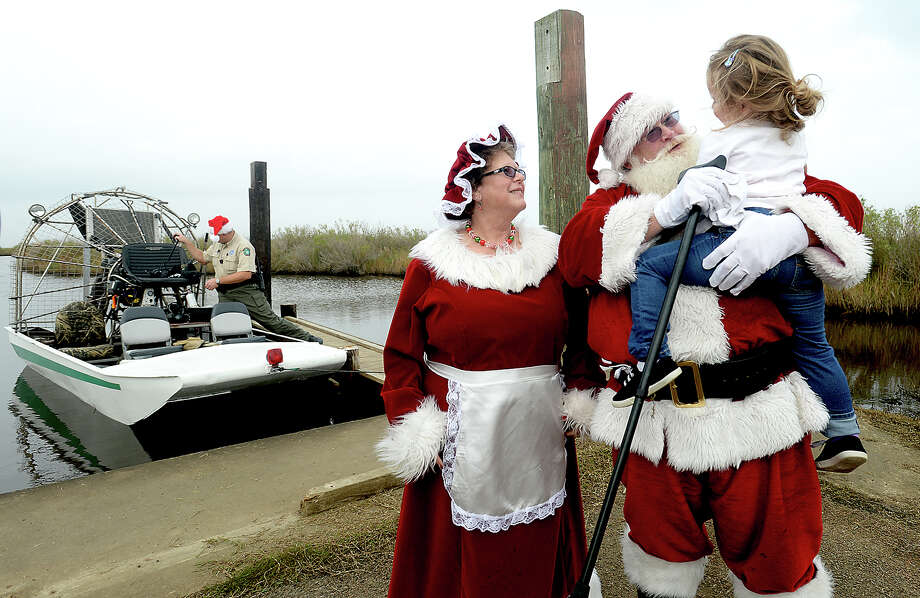 Santa and Mrs. Claus get a big hug and greeting from Bekka Butler as they arrive via airboat through the marshlands at Sea Rim State Park for the annual Very Marshy Christmas event Saturday. Hot chocolate and cookies, crafts and activities filled the afternoon as children and parents eagerly awaited Santa's arrival, with the help of driver and park superintendent Nathan Londenberg. Children then visited with the Claus's, sharing their Christmas wish lists and getting photos. Photo taken Saturday, December 17, 2016 Kim Brent/The Enterprise Photo: Kim Brent / Beaumont Enterprise
