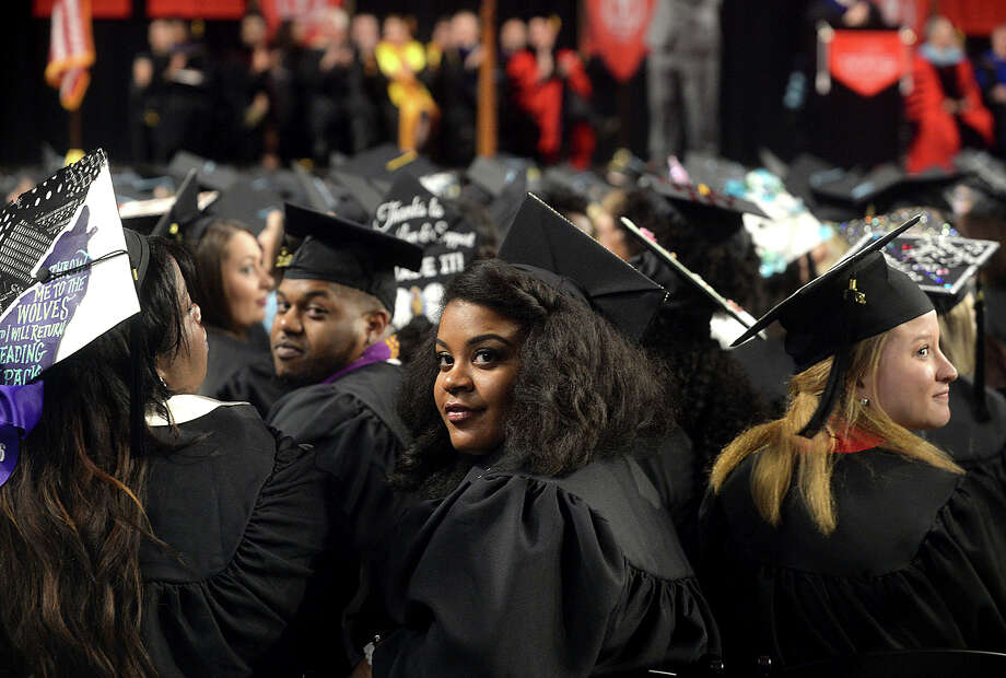 Fall graduates from Lamar University's Education and Human Development programs, including Taylor Joseph, look back at the crowd as supporting family and friends are acknowledged during Saturday's commencement ceremony at the Montagne Center. The program was one of two ceremonies held Saturday, with Fine Arts and Communication students receiving their diplomas earlier in the afternoon. Dr. James M. Simmons, who served as president of the university for 14 years, was the keynote speaker at the evening ceremony. Photo taken Saturday, December 17, 2016 Kim Brent/The Enterprise Photo: Kim Brent / Beaumont Enterprise