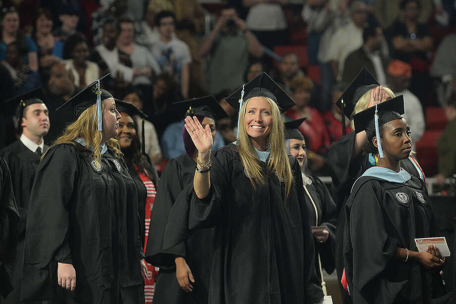Fall graduates from Lamar University's Education and Human Development programs wave to family and friends as they make their way into the arena during Saturday's commencement ceremony at the Montagne Center. The program was one of two ceremonies held Saturday, with Fine Arts and Communication students receiving their diplomas earlier in the afternoon. Dr. James M. Simmons, who served as president of the university for 14 years, was the keynote speaker at the evening ceremony. Photo taken Saturday, December 17, 2016 Kim Brent/The Enterprise Photo: Kim Brent / Beaumont Enterprise